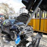 Videón a villamossal karambolozott totálkárosra tört autó Budapesten: tűzoltók mentették ki a sofőrt